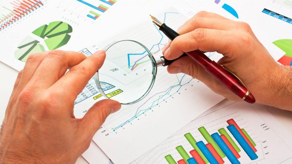 Documentos con gráficas y tablas para análisis. Detalles aumentados con una lupa.