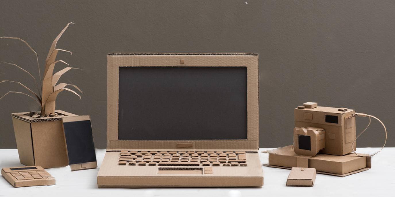imagen de herramientas diarias digitales (teléfono, ordenador) hechas en cartón.